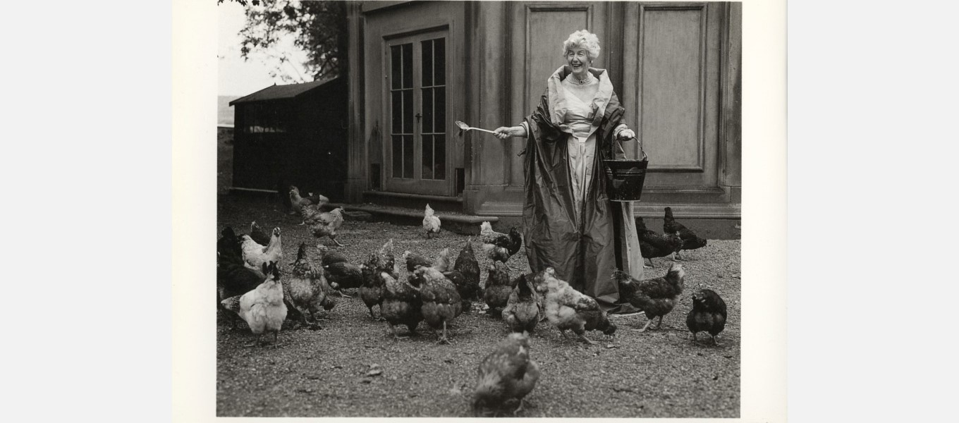 Duchess Deborah feeding her chickens outside the game larder while wearing vintage couture (c) Bruce Weber